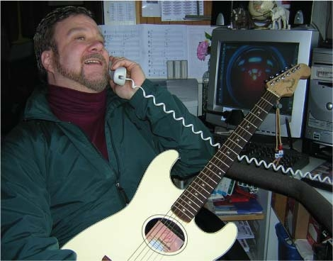 Scotty West playing guitar in his teaching studio.